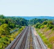Åtskillig överskrift för järnvägspår in i forested område i Burlington, Ontario, Kanada arkivbilder