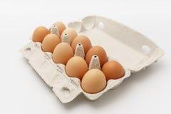 Åtskilliga ägg i kartong på en vit bakgrund Royaltyfri Bild