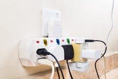 Åtskilliga elektricitetsproppar som fästas till den mång- adapteren, är dangerouen royaltyfri foto