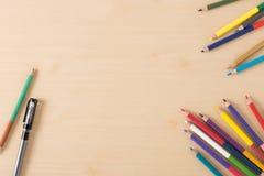 Åtskilliga färgblyertspennor på den wood texturtabellen Arkivbilder