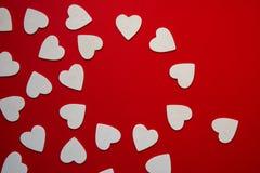 Åtskilliga hjärtaviter formar och att bilda en rund ram, röd bac Arkivbild