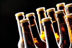 Åtskilliga kalla oöppnade ölflaskor Arkivfoto