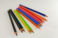 Åtskilliga kulöra blyertspennor på en vit bakgrund fotografering för bildbyråer
