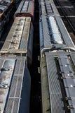 Åtskilliga linjer av dolda bilar för hopperjärnvägdrev på spår i trainyard royaltyfri foto