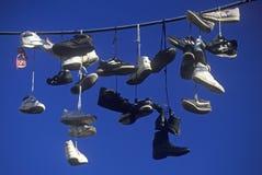 Åtskilliga par av skor som slängas över elektrisk tråd av skosnöre Royaltyfri Bild