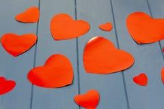 Åtskilliga röda hjärtor på en blå träbakgrund Arkivfoton