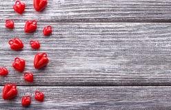 Åtskilliga röda hjärtor på grå färger målade lantlig vit träbakgrund Royaltyfri Bild