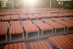 Åtskilliga rader av reclinerstolar på en semesterort Arkivbild