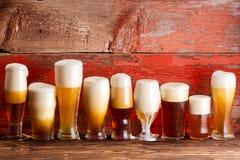 Åtskilliga skummiga halva liter för öl på lantlig träbänk Arkivfoto