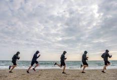 Åtskilliga sportmanklon som joggar på stranden i morgonen Fotografering för Bildbyråer