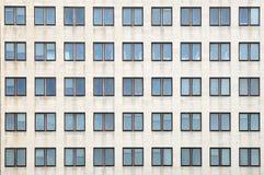 Åtskilliga stängda fönster på en stor kontorsbyggnad Royaltyfri Foto