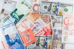 Åtskilliga valutasedlar som färgrik bakgrund Arkivbild