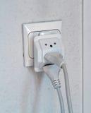 Åtskilligt elektriskt pluggar in vägguttag arkivbild