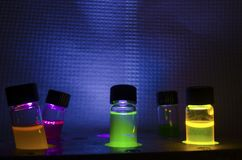 Åtskilligt färgglat slut upp fotokemisk reaktion i exponeringsglasliten medicinflaska under UV ljus i ett mörkt kemilaboratorium royaltyfri foto
