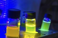 Åtskilligt färgglat slut upp ljus framkallad fotokemisk reaktion för katalysator i exponeringsglasliten medicinflaska under UV lj royaltyfri fotografi