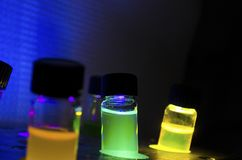 Åtskilligt färgglat slut upp ljus framkallad fotokemisk reaktion i exponeringsglasliten medicinflaska under blått UV ljus i ett m arkivfoto