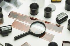 Åtskilligt fotografiska filmer och förstoringsglas på vit bakgrund royaltyfria foton