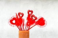 Åtskilligt valentinförälskelsesymbol i en vas Arkivbild