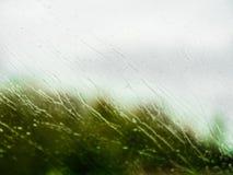 Åtskilligt vatten tappar på vindrutan på en snabb körande bil royaltyfri fotografi