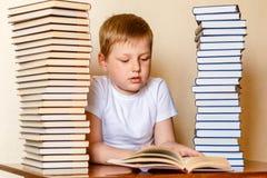 Åtta-år-gammal Caucasian pojke i en vit t-skjorta som läser en bok som sitter på tabellen royaltyfri bild