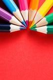 Åtta färgade blyertspennor i en halvcirkel på röd bakgrundsmakro Royaltyfri Foto