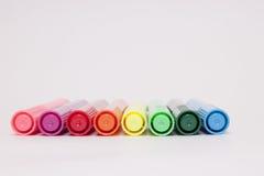 Åtta färgrika pennor som ligger på ett vitt ark Royaltyfri Foto