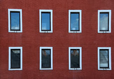 Åtta Windows på väggen för röd tegelsten Arkivbilder
