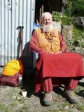 Åttio år gammal munk som kopplar av på solen - Nepal Arkivbilder
