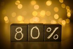 80% åttio procent teckenkrita som är skriftlig på svartkuber på suddig bokehbakgrund royaltyfri fotografi