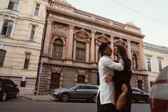 恋人一对年轻,性感的夫妇为在街道上的一台照相机摆在 免版税库存照片