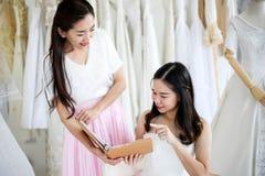 换衣服由她的最好的朋友在她的婚礼那天和选择一婚纱的美丽的新娘在商店和商店 免版税库存图片