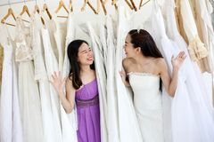 换衣服由她的最好的朋友在她的婚礼那天和选择一婚纱的美丽的新娘在商店和商店 免版税库存照片