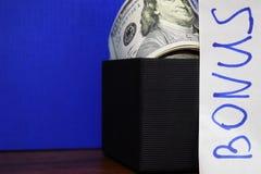捆绑在蓝色背景隔绝的礼物盒的美元,题字奖金 免版税库存照片