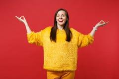 握在瑜伽姿态,放松的思考的黄色毛皮毛线衣的微笑的年轻女人手被隔绝在红色墙壁 免版税库存图片