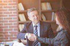 握手在桌面附近的商务伙伴在办公室 库存图片