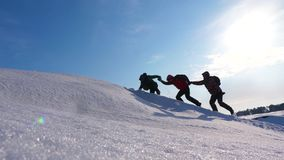 握手的登山人帮助攀登多雪的小山 妥善协调的配合在冬天旅游业方面 队  股票录像