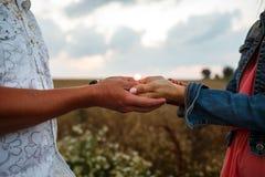 握手的男人和妇女走在领域在日落 免版税图库摄影