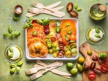 板材用鲜美吃的五颜六色的切的蕃茄 在厨房用桌上的地中海成份 顶视图 免版税库存照片