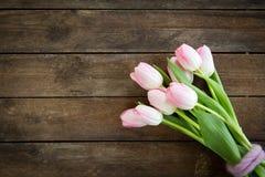 束在桃红色的郁金香在棕色木背景 免版税库存照片