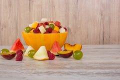 桃子,西瓜,瓜,莓,李子,葡萄,在瓜色拉盘的切成小方块的谎言 库存图片