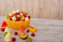 桃子,西瓜,瓜,莓,李子,葡萄,在瓜色拉盘的切成小方块的谎言 库存照片