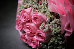 桃红色上升了在黑水泥背景的花束 库存图片