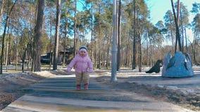 桃红色夹克和镶边帽子奔跑的一女孩沿道路在春天妈妈的容忍和微笑的公园 影视素材