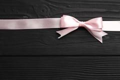 桃红色弓和丝带在黑木背景 免版税库存照片