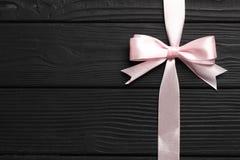 桃红色弓和丝带在黑木背景 免版税库存图片