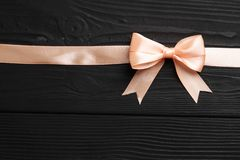 桃红色弓和丝带在黑木背景 库存照片
