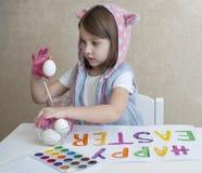 桃红色兔宝宝耳朵的愉快的复活节女孩画家用五颜六色的被绘的鸡蛋 孩子为复活节做准备 手画 免版税库存照片