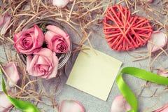 桃红色玫瑰以水、柳条心脏、装饰品和一种空的形式笔记的关于桌 库存照片