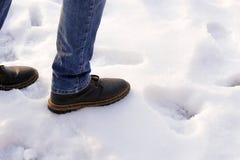棕色靴子和蓝色牛仔裤的人desided做第一步到朦胧在雪 复制空间 在雪以后的第一步 库存照片