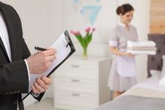 检查佣人工作的家务经理在酒店房间 免版税库存图片